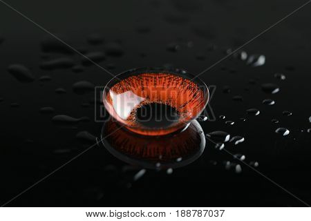 Red contact lens on wet black background