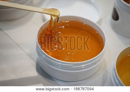 Container with liquid sugar for epilation on table