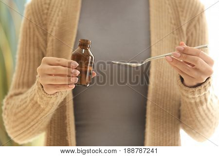 Woman holding bottle with cough syrup and spoon, closeup