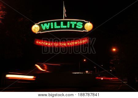 WILLITS, CALIFORNIA, USA - September 1, 2009: Neon Willits, Gateway to the Redwoods, sign hang above Highway 101 as a car drives underneath