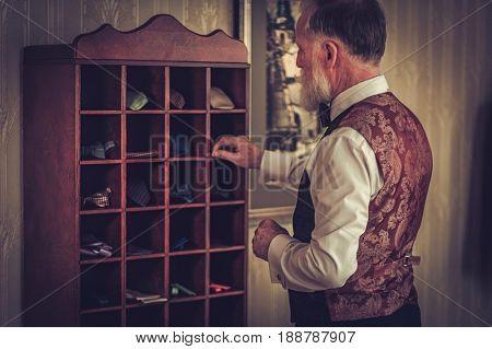 Senior man choosing custom made bow ties and neckties.