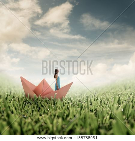 A pretty girl in a pale blue dress stands in a pink origami boat, peacefully breathing clean crisp spring air