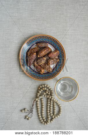 Ramdan food and Islamic religious objects. Sweet dates, glass of drinking water and prayer beads. Fast is ended with sweet dates and glass of water after sunset during holy month of Ramadhan.