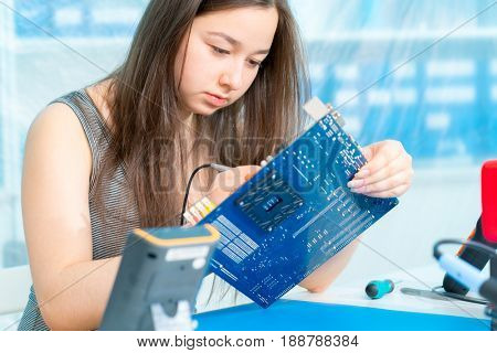 School girl in robotic class with PCB