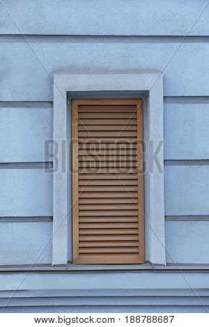 Window with closed blinds on old blue building
