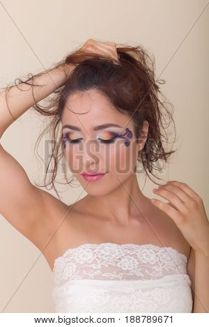 Young brunette fashion model with colorful extravagant eye make-up