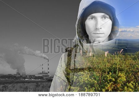 Face of young man hiker, steaming industrial smokestacks and green natural landscape. Double exposure effect photography.