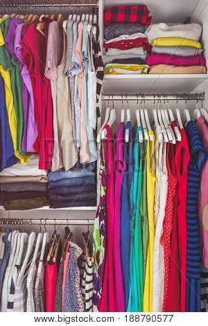 Home closet bedroom clean wardrobe of women fashion clothing hanging on racks. Woman clothes.