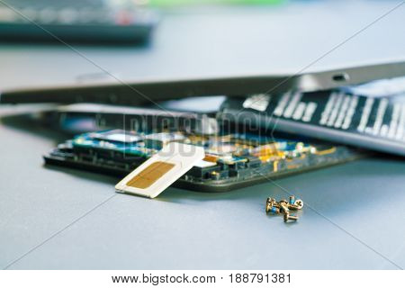 Disassembled mobile phone in the service center with internal components of the camera and speaker