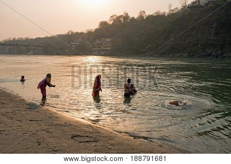 LAXMAN JHULA, INDIA - APRIL 15, 2017: People are taking a bath in the  holy river Ganges in Laksman Jhula on the 15th april 2017 in India