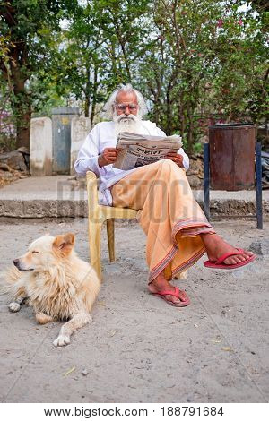 LAXMAN JHULA, INDIA - APRIL 20, 2017: A Hindu swami sitting reading the newspaper in Laxman Jhula on the 20th april 2017 in India
