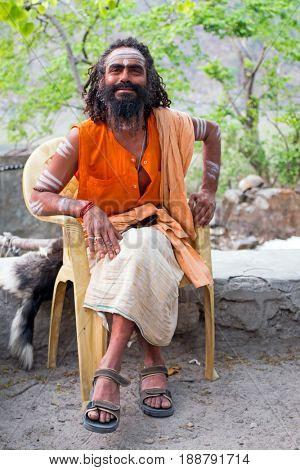 LAXMAN JHULA, INDIA - APRIL 20, 2017: A Hindu sadhu sitting in the streets in Laxman Jhula on the 20th april 2017 in India Asia