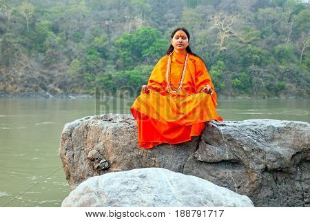 LAXMAN JHULA, INDIA - APRIL 19, 2017: A Hindu saint in orange sitting in meditation on a rock at the holy river Ganges in Laxman Jhula on the 19th april 2017 in India Asia