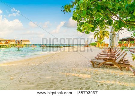 Beach chairs with umbrella at Maldives island, white sandy beach and sea