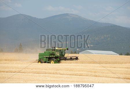 Spokane, WA - August 2, 2016: Farmer harvesting crop in a wheat field near Mt. Spokane, WA. Editorial
