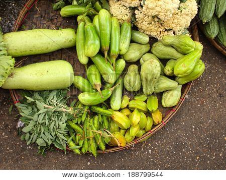 Fresh vegetables in wicker basket  - cucumber, onion, bitter gourd, green beans, squash, salad, carambola, on morning chinese market, Yangon, Myanmar (Burma)