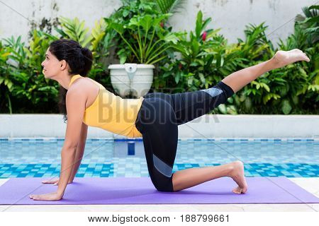 Fit young woman exercising with one raised leg for lower body workout