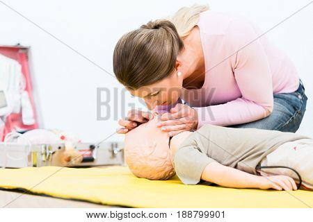 Woman in first aid course practicing revival of infant on baby doll