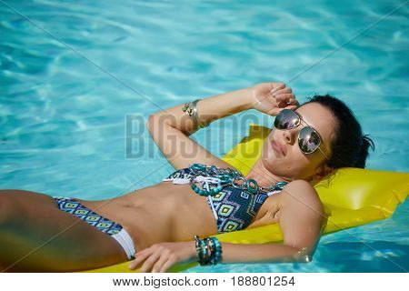 A woman in the pool floats on a blown mattress