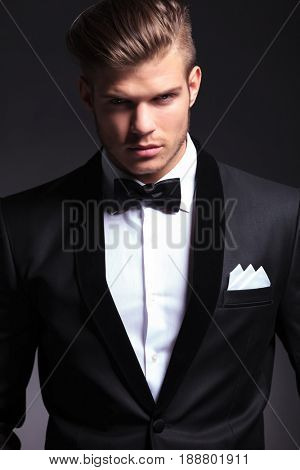 closeup portrait of an elegant young fashion man in tuxedo looking at the camera with a serious expression.on black background