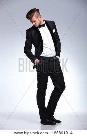 full length photo of an elegant young fashion man in tuxedo looking down while with hands in pockets .on gray background
