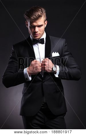 elegant young fashion man is holding his hands on his tuxedo jacket while looking away from the camera. on black background