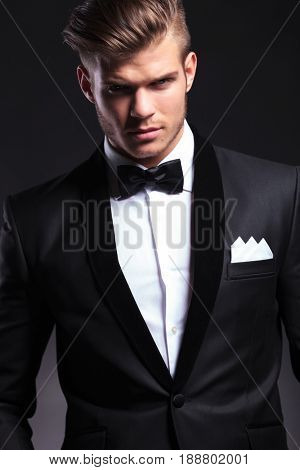 cutout portrait of an elegant young fashion man in tuxedo looking at the camera. on black background