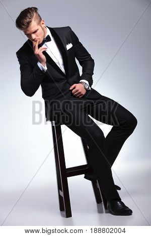 elegant young fashion man in tuxedo smoking a cigar and looking down while sitting on a high stool . on gray background