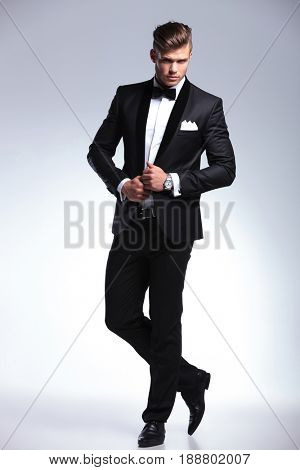 full length picture of an elegant young fashion man with his hands on his tuxedo jacket is looking at the camera with a serious expression. on gray background