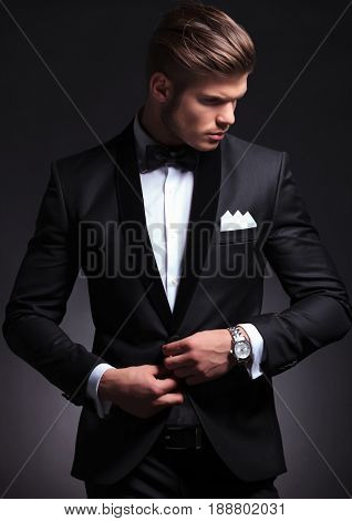 elegant young fashion man buttoning his tuxedo jacket while looking at his side, away from the camera. on black background