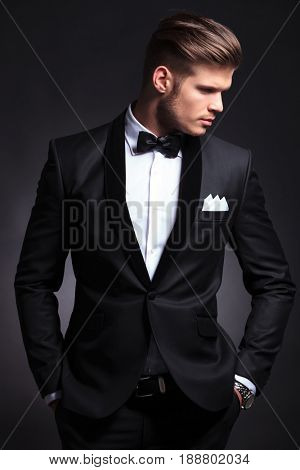 elegant young fashion man in tuxedo looking to his side while holding his hands in his pockets .on black background