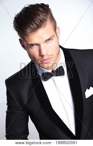 closeup view of an elegant young fashion man in tuxedo looking at the camera with a fierce expression. on gray background