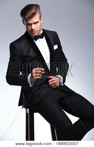 seated elegant young fashion man in tuxedo looking at the camera while holding a cigar between his fingers. on gray background
