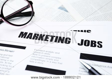 Paper sheet with text MARKETING JOBS, closeup