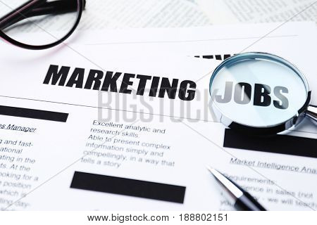 Paper sheet with word JOBS through magnifier, closeup. Marketing concept
