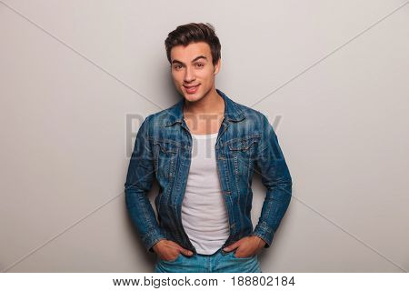 relaxed casual man in jeans jacket smiling for the camera in studio