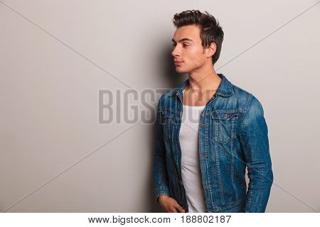 side view of casual man in jeans jacket looks away on grey background
