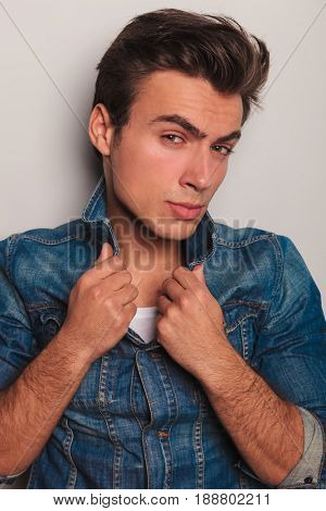 cool young man holding jacket's collar against grey studio background