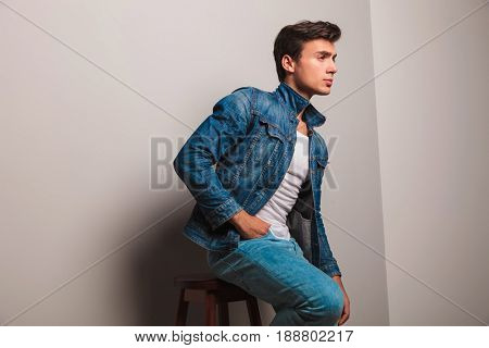 seated casual man in jeans clothes looks away to side on grey background