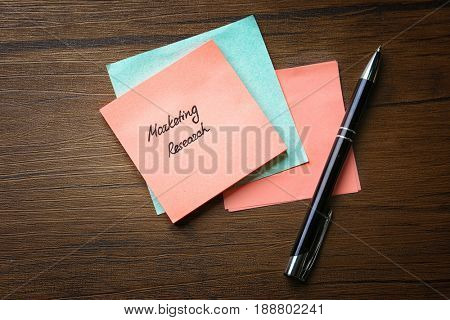 Paper note with text MARKETING RESEARCH on wooden background