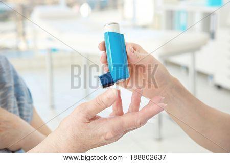 Doctor giving elderly woman inhaler in clinic