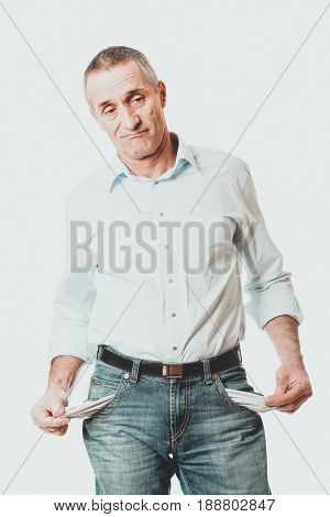 Confused man showing his empty pockets