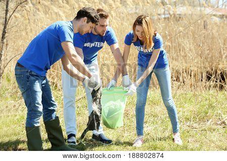 Young volunteers gathering garbage outdoors