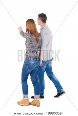 Back view of walking young couple (man and woman) pointing. Isolated over white background/ pressed shoulders man and woman go and point out the finger on the target path