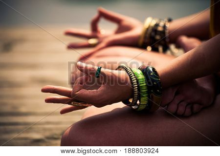 woman in a meditative yoga position sit on wooden pontoon on the lake wearing lot of bracelets and rings lower body