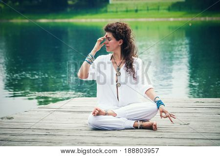 young woman wearing white comfortable clothes practicing yoga breathing technique  by the lake worm summer spring day