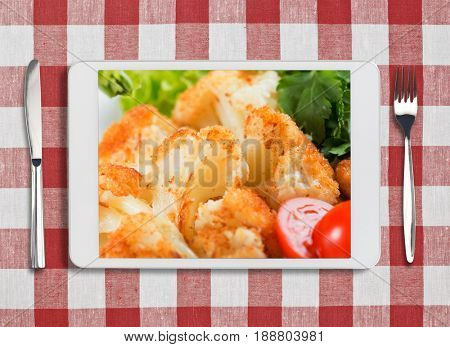 tablet pc with dish, fork and knife on red checked tablecloth