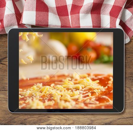 black tablet pc with pizza displayed on wooden table and picnic tablecloth