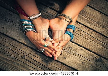 closeup of girl feet and hands with lot of boho style bracelets, rings and anklets outdoor summer day on wooden background