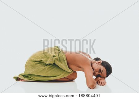 Woman curled up wrapped in towel